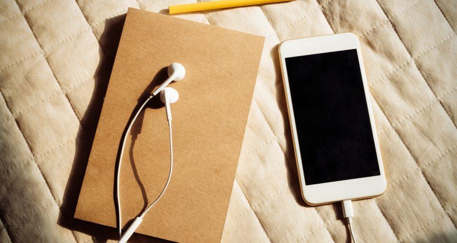 Buch mit Kopfhörern und Handy